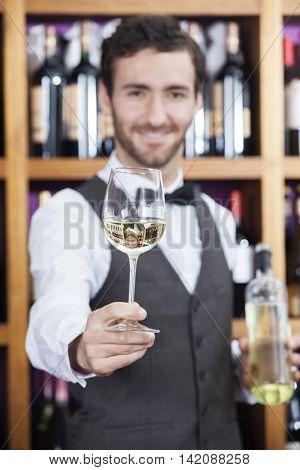Bartender Offering White Wine Glass Against Shelves