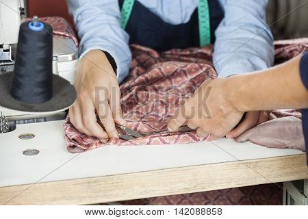 Tailor Instructing Employee In Sewing Factory