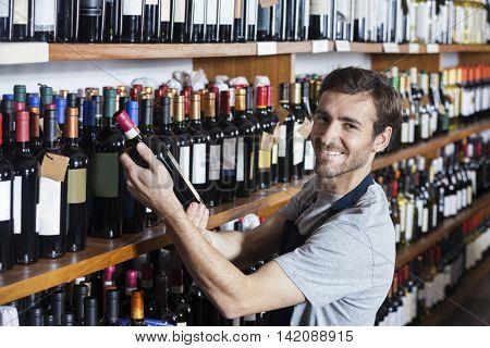 Smiling Salesman Arranging Wine Bottle On Shelf