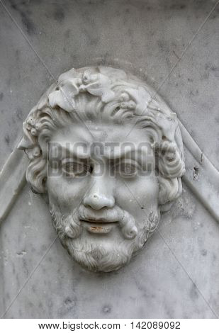 marble bas-relief in the form of ancient man face with beard on wall of vase
