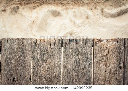 Topical wooden planked surface with sandy beach on background and copy space