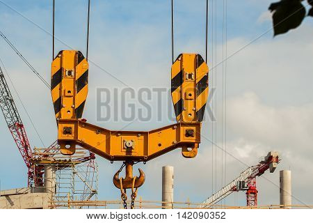 Construction site of football stadium for football championship. Crane hoist and hook with wire rope sling against the background of blue sky, construction concept