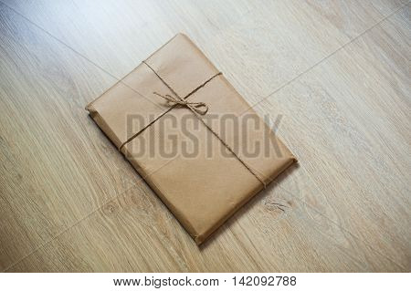wrapped gift kraft paper on a wooden background.