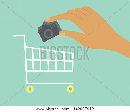 Hand adds camera to a shopping cart Online shopping concept