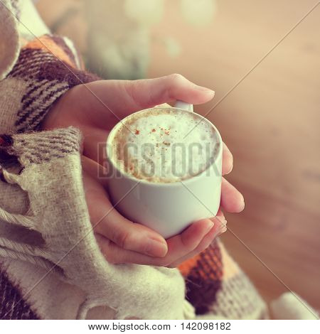 frothy cappuccino with cinnamon hands are bundled up in a warm blanket / warm retro coffee break