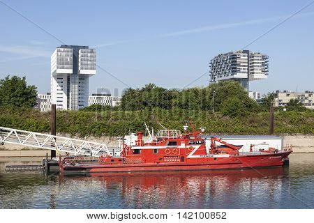 COLOGNE GERMANY - AUG - 7 2016: Fire rescue boat and the modern crane buildings in Cologne North Rhine-Westphalia Germany