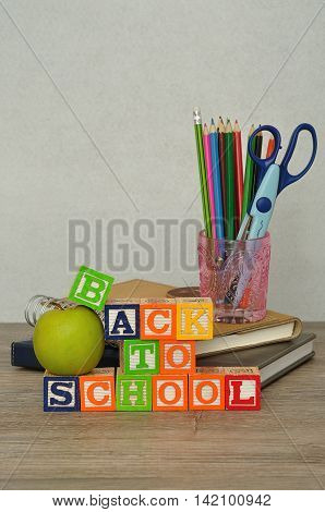 The words back to school spelled with colorful alphabet blocks displayed with a glass filled with coloring pencils and a scissor and a green apple on a table with a white background
