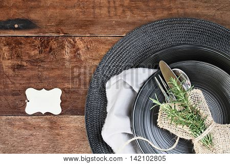 Tied bundle of Rosemary Herbs Silverware and burlap napkin with black place setting over rustic wooden table made of weathered barn wood. Image shot from overhead. Blank place card for your text.