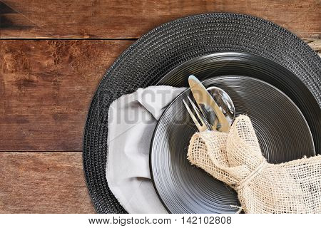 Silverware and burlap napkin with black place setting over rustic wooden table made of weathered barn wood. Image shot from overhead.