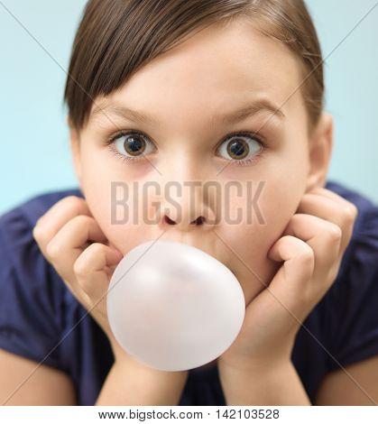Little girl is blowing big bubble gum, closeup portrait