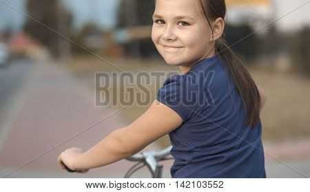 Cute girl is sitting on bicycle, outdoor portrait