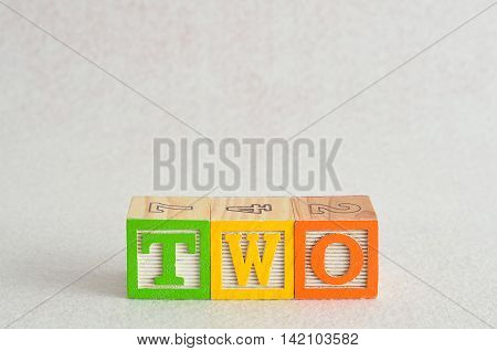The word two (2) spelled with colorful alphabet blocks isolated against a white background