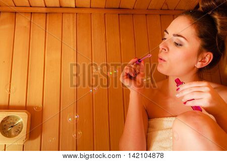 Woman Relaxing In Sauna Room Blowing Soap Bubbles