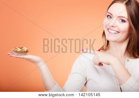 Smiling Woman Holds Cake In Hand Pointing With Finger
