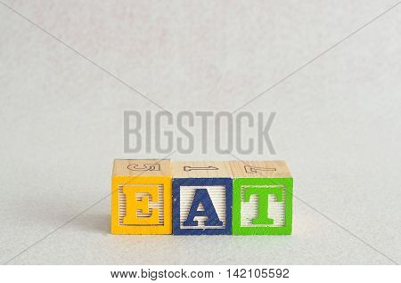 The word eat spelled with colorful alphabet block isolated on a white background