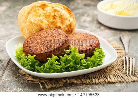 two vegetarian burgers with potato bun and salad.