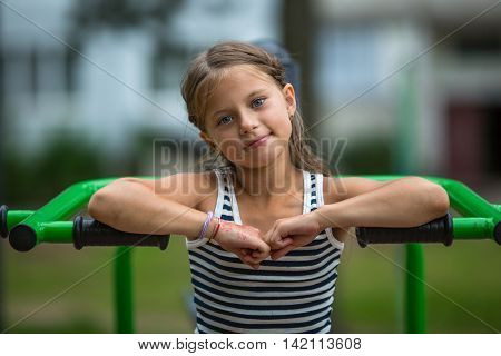 Portrait of little girl sitting on exercise equipment in the public park.