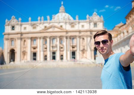 Happy man taking selfie in Vatican city and St. Peter's Basilica church, Rome, Italy