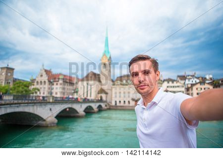 Young man taking selfie background famous Fraumunster Church and river Limmat.
