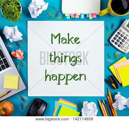 Make things happens. Office table desk with supplies, white blank note pad, cup, pen, pc, crumpled paper, flower on blue background. Top view