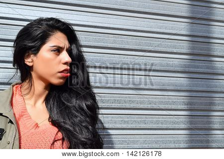 Portrait of young latin woman outdoors. Trendy and urban clothes. Copyspace.