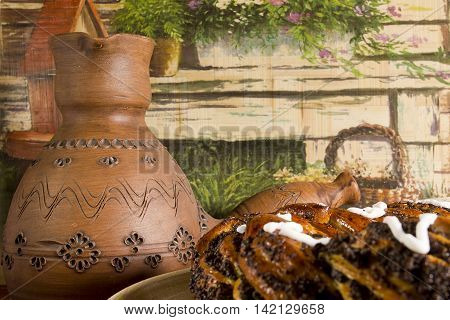 Clay pots for coffee and a roll with poppy seeds on a rustic background