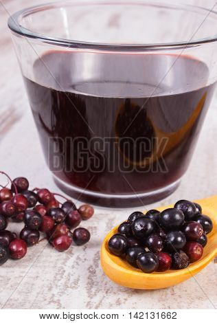 Fresh Elderberry With Wooden Spoon And Juice On Old Wooden Background, Healthy Nutrition