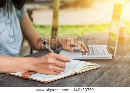 Female hands with pen writing notebook and using laptop on desk table at coffee shop.