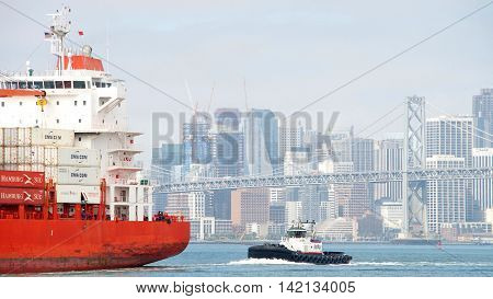 Oakland CA - August 08 2016: Tugboat REVOLUTION at the stern of Cargo Ship CAP PALMERSTON assisting the vessel to maneuver into the Port of Oakland. City of San Francisco in the background.