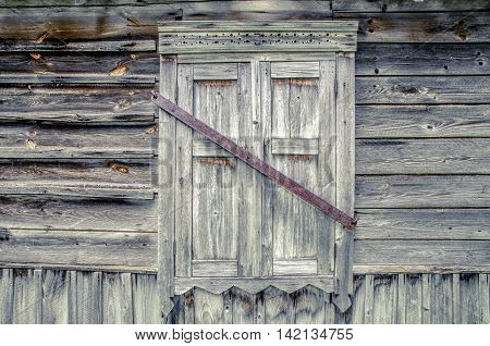 closed window shutters on a wooden wall