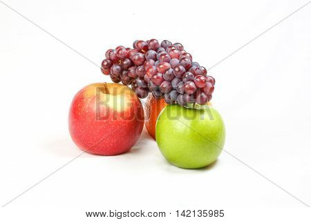 Small red grapes bunch orange red and greed apple on white background