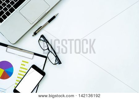 White office desk table with blank screen smartphone calculator chart or graph over backboard laptop eyeglasses and pen. Top view with copy space