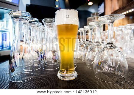 Glass of light beer on a table between empty glasses on front bar in pub