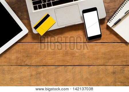 Office desk table with laptop blank screen smartphone credit card blank screen tablet pen and leather notebook. Top view with copy space.