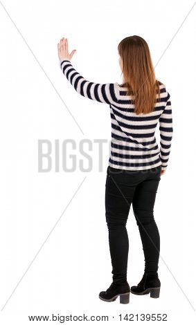 back view of young woman presses down on something. Isolated over white background. Rear view people collection. backside view of person. Girl in a striped jacket stands sideways and presses his hand