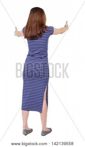 Back view of  woman thumbs up. Rear view people collection. backside view of person. Isolated over white background.  The brunette in a blue striped dress shows thumbs up with both hands.