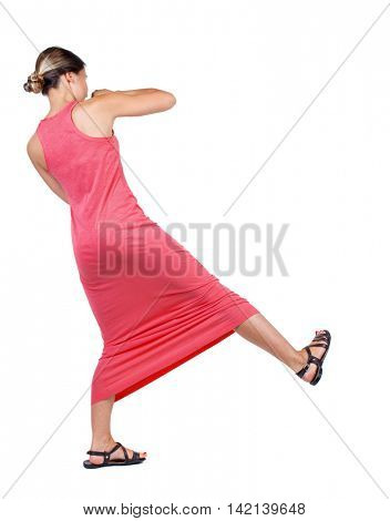 skinny woman funny fights waving his arms and legs. Isolated over white background. A slender woman in a long red dress swinging leg