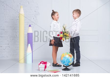 Student gives tulips to his girlfriend on the day of knowledge. The concept of sympathy in children
