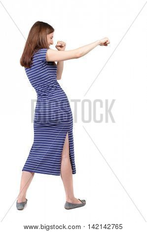 skinny woman funny fights waving his arms and legs. Isolated over white background. The brunette in a blue striped dress stands sideways and hit a hand ..