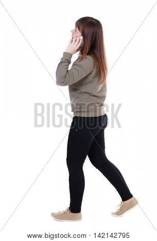 side view of a woman walking with a mobile phone. back view of girl in motion.  backside view of person.  Rear view people collection. Isolated over white background. A girl in a gray jacket talking