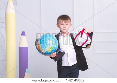 Schoolboy with a globe and books on the background of large pencils. Concept of the day of knowledge