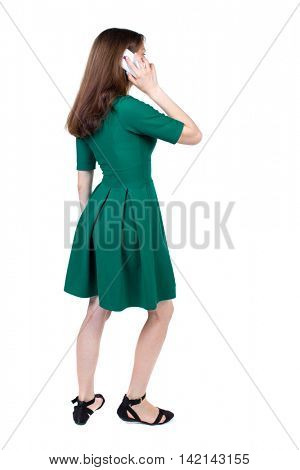 side view of a woman walking with a mobile phone. back view of girl in motion.  backside view of person.  Rear view people collection. Isolated over white background. The slender brunette in a green