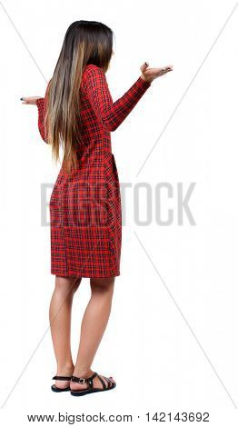 Back view of angry young woman Rear view. isolated over white. backside view of person.  Rear view people collection. Isolated over white background. The girl in red plaid dress throws his hands in