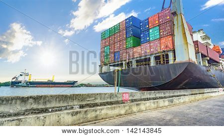 The containers cargo on the container ship in the harbor with the river and sea and cloudy sky.