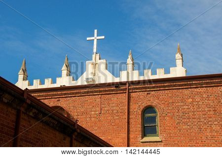 NEW NORCIA,WA,AUSTRALIA-JULY 15,2016: Cross detail over the the brick Spanish gothic St. Ildephonsus College for Boys in New Norcia, Western Australia.