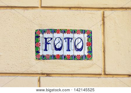 Word foto on decorative ceramic tiles on the wall outdoors