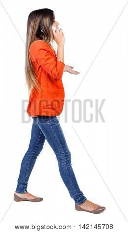 side view of a woman walking with a mobile phone. back view of girl in motion.  backside view of person.  Rear view people collection. Isolated over white background. girl in a red jacket goes