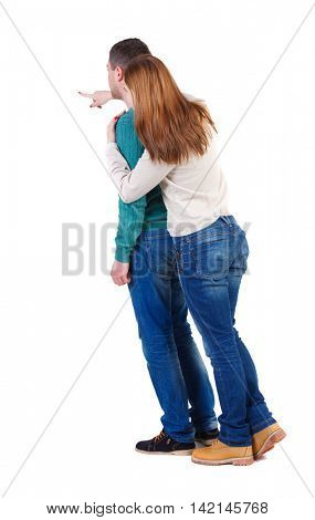 young couple pointing at wal Back view  (woman and man). Rear view people collection.  backside view of person.  Isolated over white background. A woman in a white blouse and hugged a man shows his