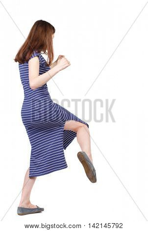 skinny woman funny fights waving his arms and legs. Isolated over white background. The brunette in a blue striped dress fighting and kicking.