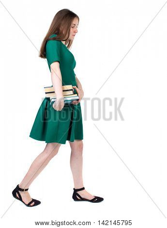 Girl comes with  stack of books. side view. Rear view people collection.  backside view of person.  Isolated over white background. The slender brunette in a green short dress sadly goes to the side